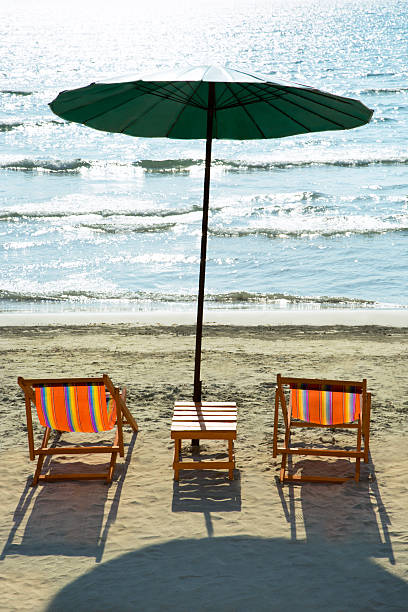 beach chairs and umbrella on beach. - dawdle stock pictures, royalty-free photos & images
