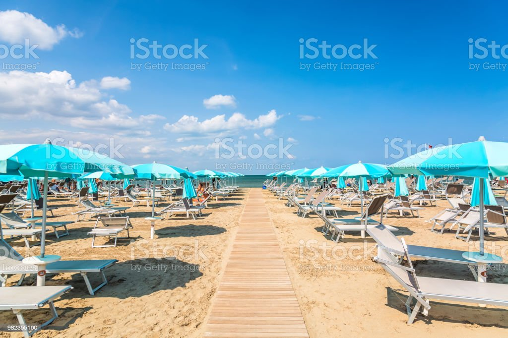 Beach chairs and umbrellas in Rimini, Italy during summer day with blue sky. Summer vacation and relax concept. stock photo