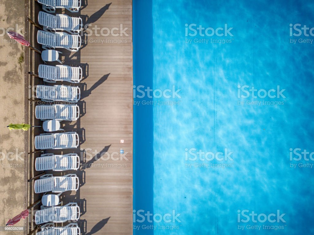 Top view of a condo swimming pool with white sun beds in a row for...