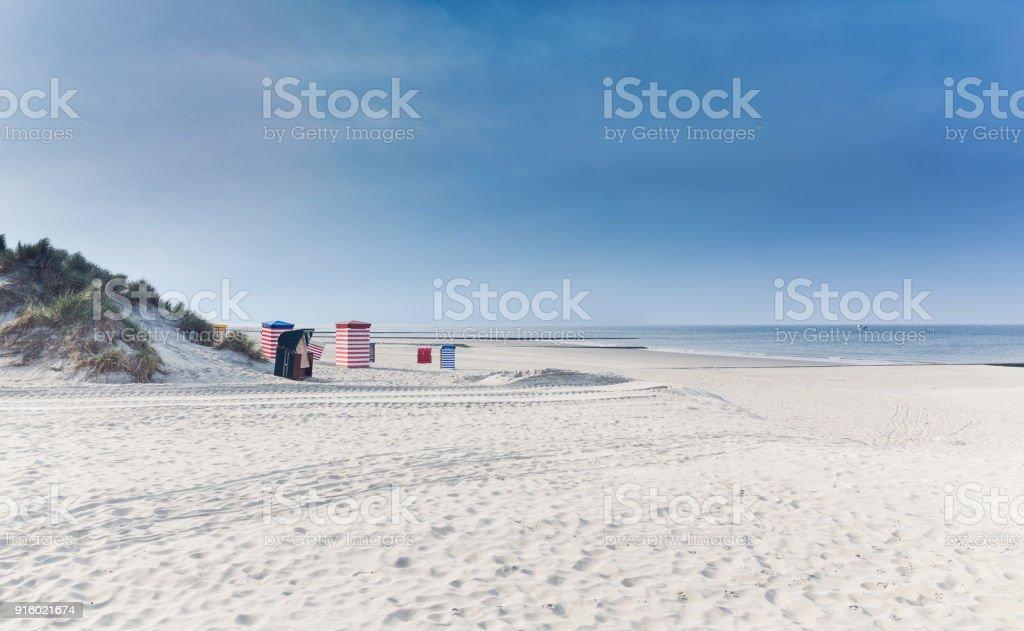Strandkörbe auf der Insel Borkum mit Sand und ein blauer Himmel – Foto