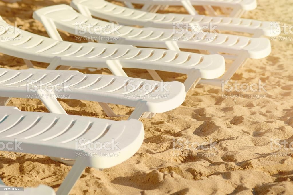 Beach chairs on the sand. Several free white beach chairs on the beach stock photo