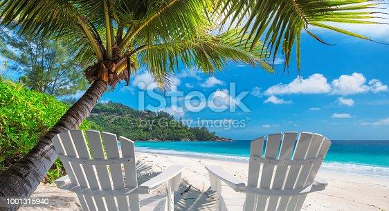 istock Beach chairs on tropical beach 1001315940