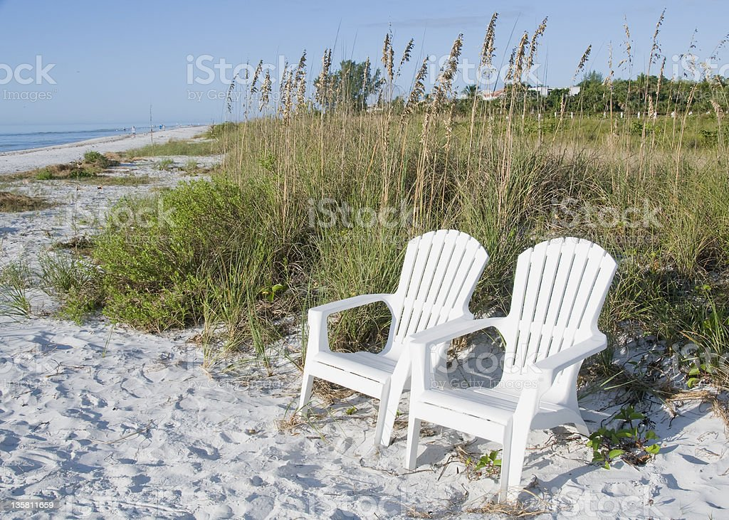 Beach chairs on white sand stock photo