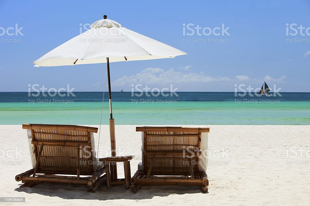 Beach chairs overlooking white sandy beach and turquoise sea royalty-free stock photo