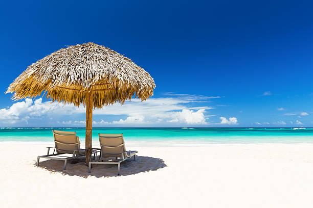 Beach chairs with umbrella and beautiful sand beach stock photo