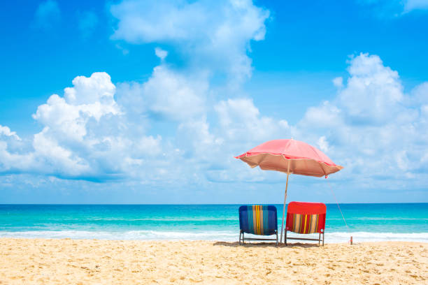 Beach chairs with umbrella and sand beach in summer. stock photo