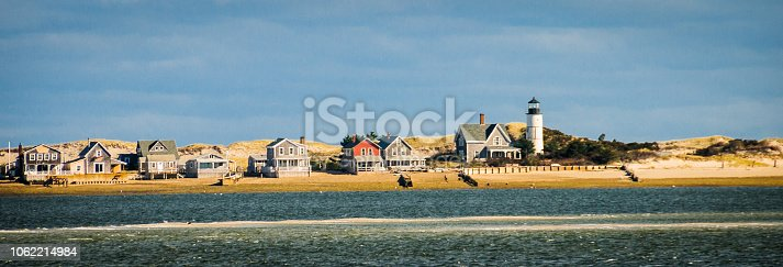 Summer cottages and a lighthouse are nestled in the sand dunes of Sandy Neck peninsula off the coast of Barnstable, Massachusetts.