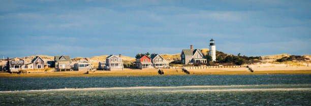Beach Colony Summer cottages and a lighthouse are nestled in the sand dunes of Sandy Neck peninsula off the coast of Barnstable, Massachusetts. cape cod stock pictures, royalty-free photos & images