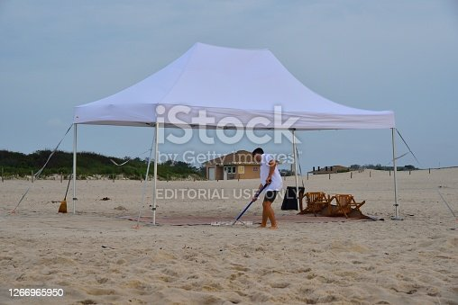 A young adult male is using a rake to groom and clean up the area around a beach canopy that he has claimed for his families shelter on assateague island national seashore this overcast August pre-dawn scene.  I call him a beach comber