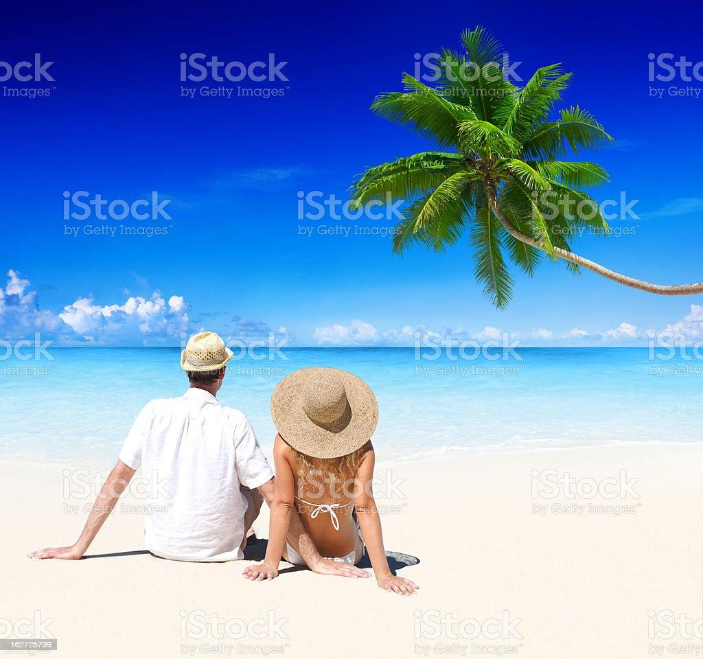 Beach couple, blue seas, blue skies and palm tree royalty-free stock photo