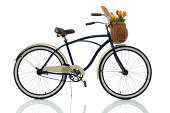 Beach cruiser with basket that has tulips and bread in it isolated on white side view