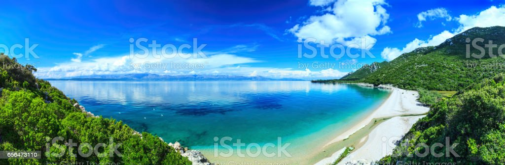 Beach, crystal clear water in Adriatic Sea and Green Mountains stock photo
