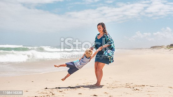 Shot of an adorable little boy having fun with his mother at the beach