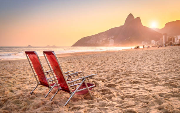 Beach deck chair against a backdrop of Two Brothers Mountain in Rio de Janeiro, Brazil stock photo