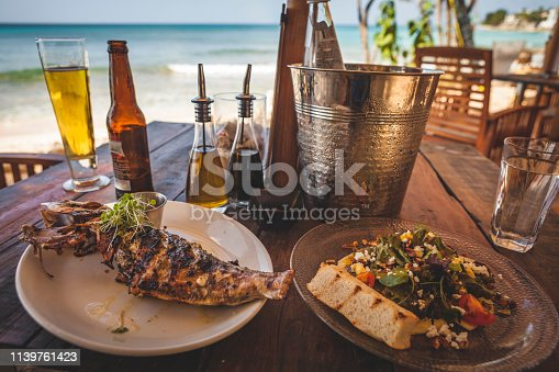 Caribbean, Grilled fish and salad lunch layed out on a beachside table