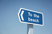 Beach Direction Sign against bright blue sky