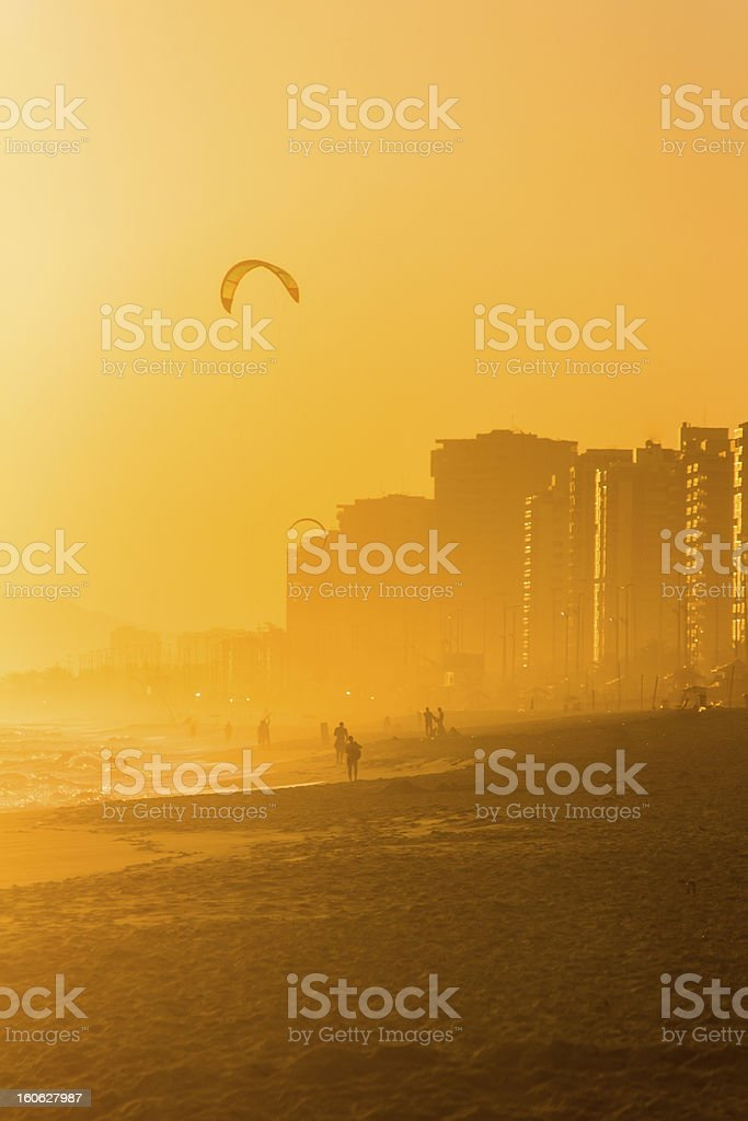 Beach during sunset with people and kitesurfing stock photo