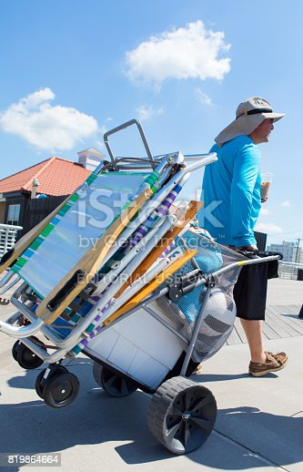 Long Beach, New York - July 16, 2017: Beach goer dragging a beach cart filled with beach essentials like chairs cooler and toys on the boardwalk of Long Beach in Long Island NY.