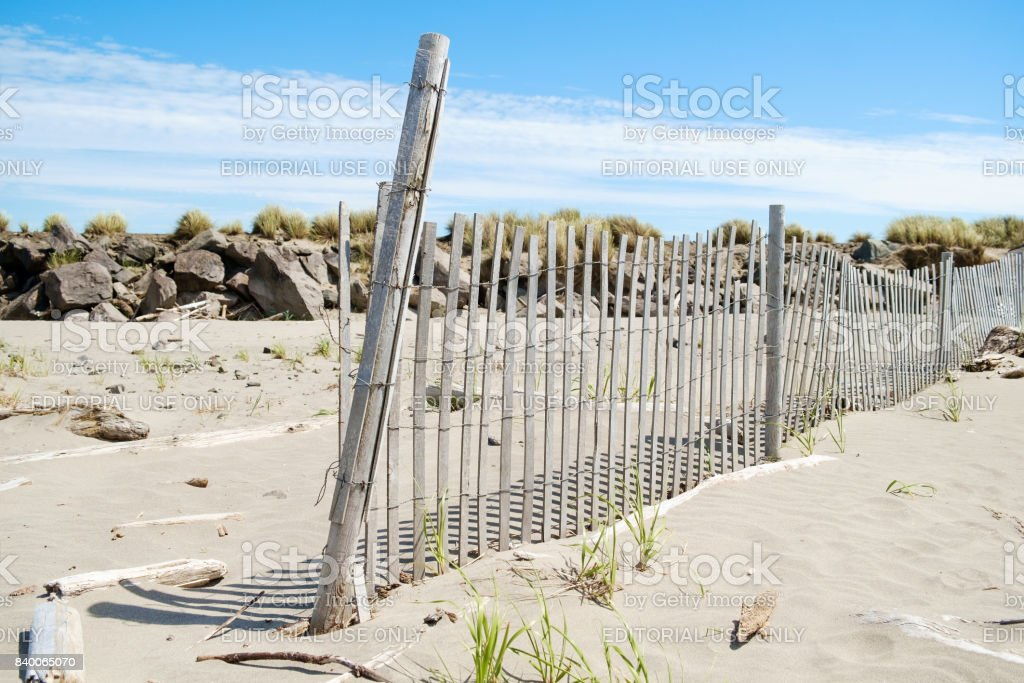 Beach fence in sand stock photo