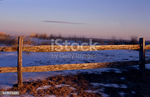 wooden fence on a beach in late afternoon light