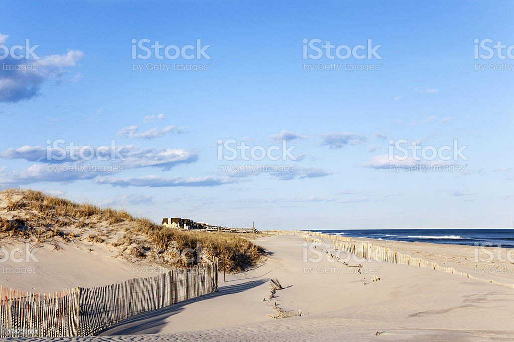 Beach Fence, Sand, Houses and the Ocean. stock photo