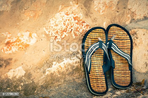 959792752 istock photo Beach flip-flops on the old wall background 512296282