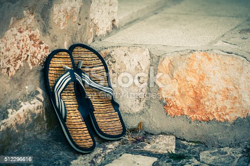959792752 istock photo Beach flip-flops on the old wall background 512296616
