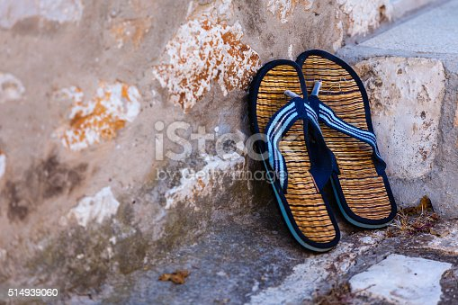 959792752 istock photo Beach flip-flops on the old wall background 514939060
