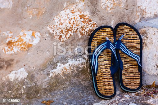 959792752 istock photo Beach flip-flops on the old wall background 514939682