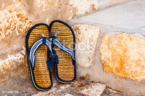 959792752 istock photo Beach flip-flops on the old wall background 517495726