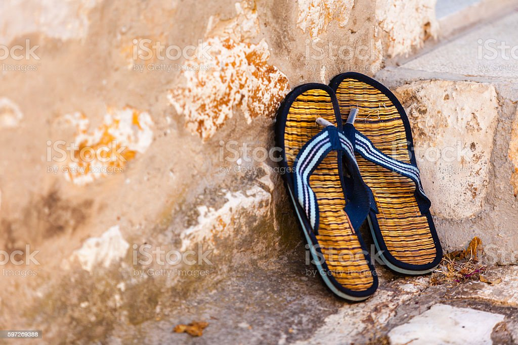 Beach flip-flops on the old wall background royalty-free stock photo