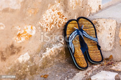 959792752 istock photo Beach flip-flops on the old wall background 597269388