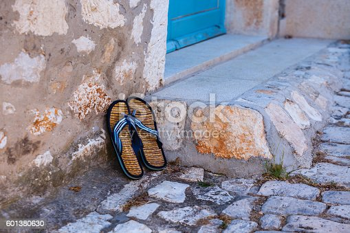 959792752 istock photo Beach flip-flops on the old wall background 601380630