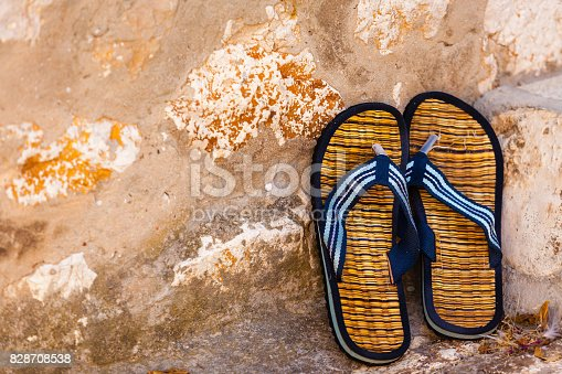 959792752 istock photo Beach flip-flops on the old wall background 828708538