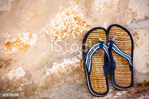 959792752 istock photo Beach flip-flops on the old wall background 828709498