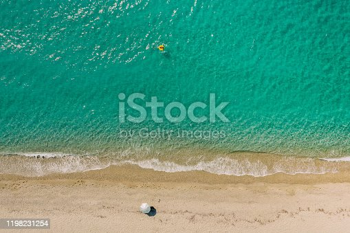 Photo of a beach from above and young woman relaxing on inflatable ring in the sea