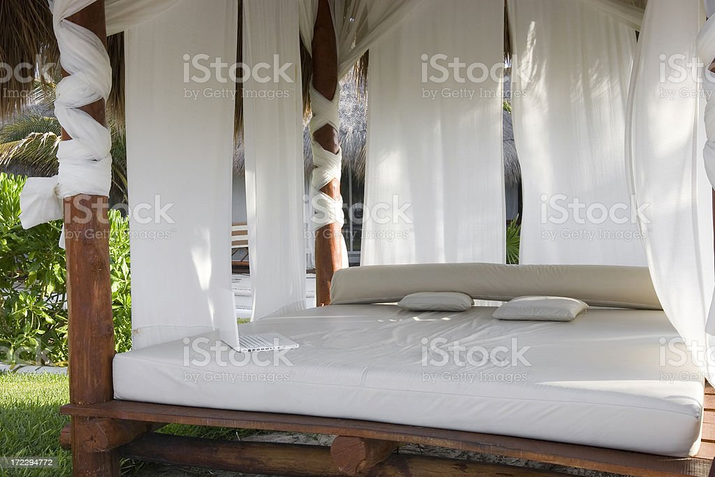 Beach Front Empty Tropical Cabana Bed with Laptop, Copy Space royalty-free stock photo
