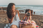 Mother photographing little daughter at the beach with instant camera