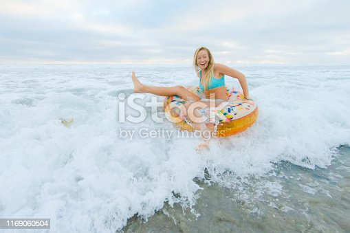 Young woman having fun at the beach with a donut themed inflatable ring