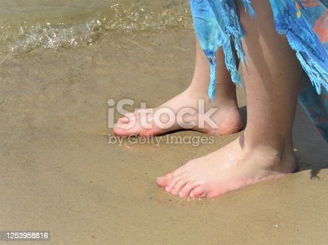 Girl's bare feet on sand at water's edge. Copy space.