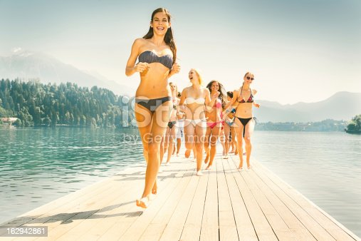 Attractive group of girls in bikinis running over jetty at a beautiful lake on a sunny summer day. Fun, Lifestyle Action Teenage Group Portrait. 60s Style Technicolor-Polaroid washed-out colors. Edited, Toned, Masked, Colorized.