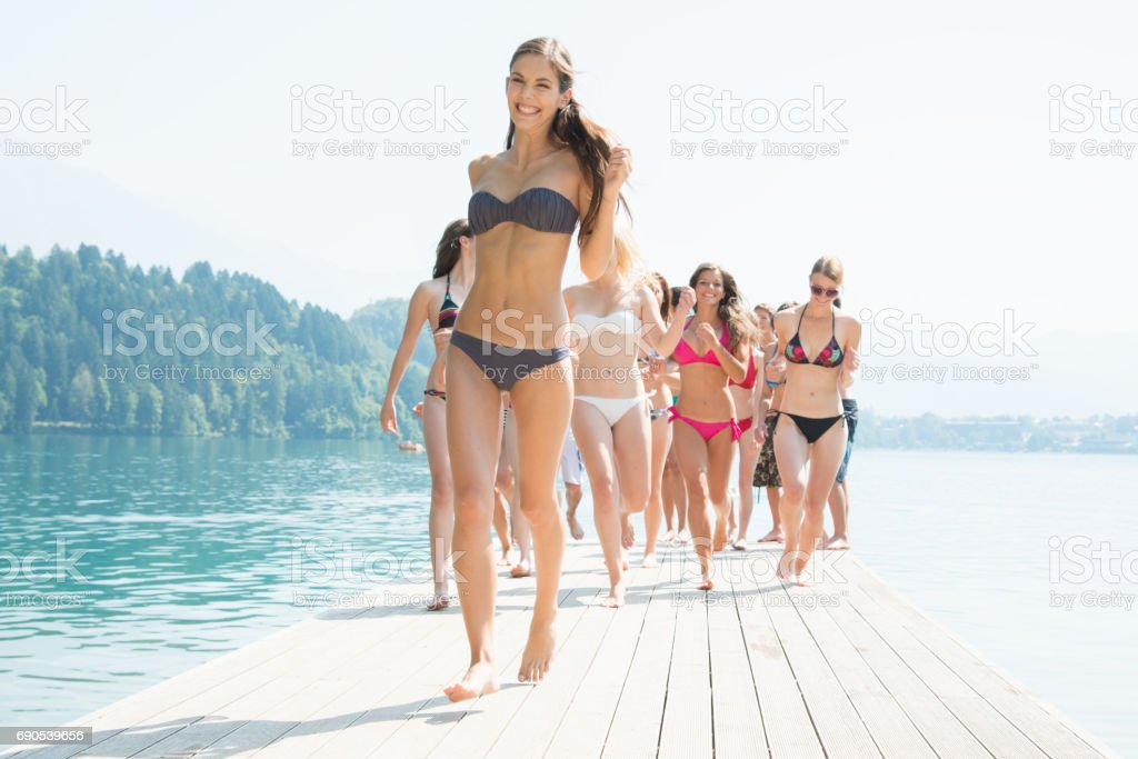 Beach girls walking along on jetty at the lake – Foto