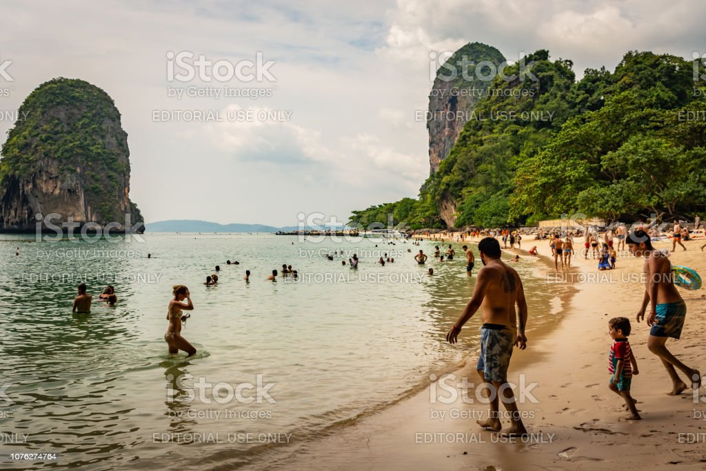 Beach Hat Phra Nang near Krabi, Thailand, sunny beach, crowd of people, bathing tourists, green trees and clouds in the background – zdjęcie