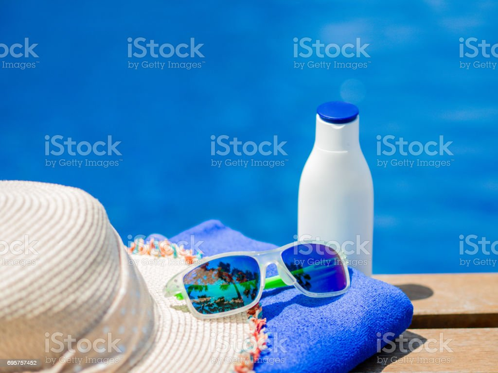 Beach hat, sunglasses, blue towel and sunscreen at the side of swimming pool. Vacation, beach, summer travel concept stock photo
