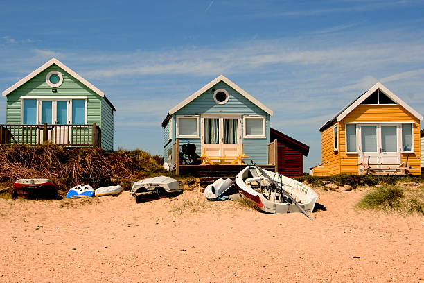 Beach holiday Beach huts and boats by the sea beach hut stock pictures, royalty-free photos & images