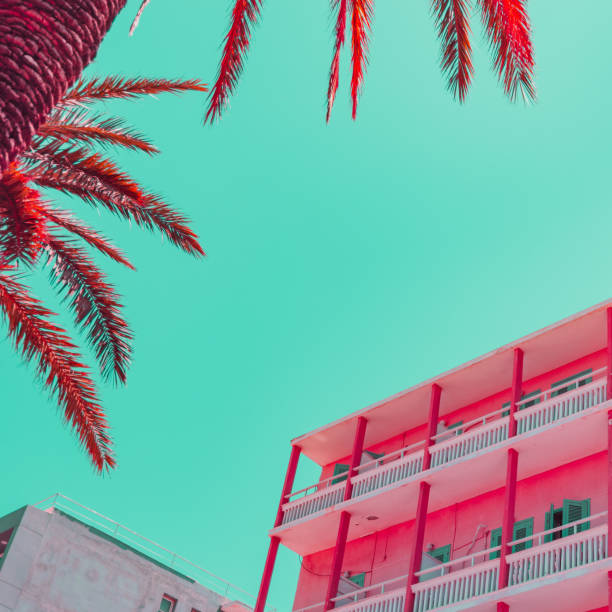 Beach hotel and part of palm leaves in infrared style. Tropical travel concept. Minimalism and surreal. Soft light colors