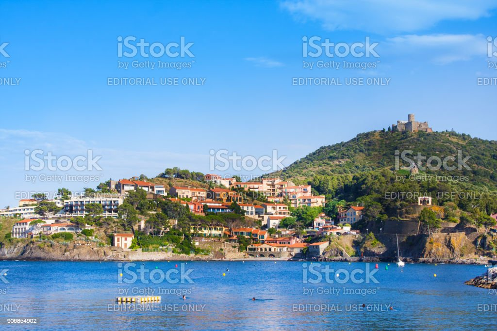Beach hotels in Collioure village with a windmill at the top of the hill, Roussillon, Vermilion coast, Pyrenees Orientales, France stock photo