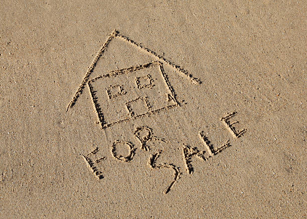 Beach House For Sale A beach house for sale concept, drawn in the sand at the beach. beach hut stock pictures, royalty-free photos & images