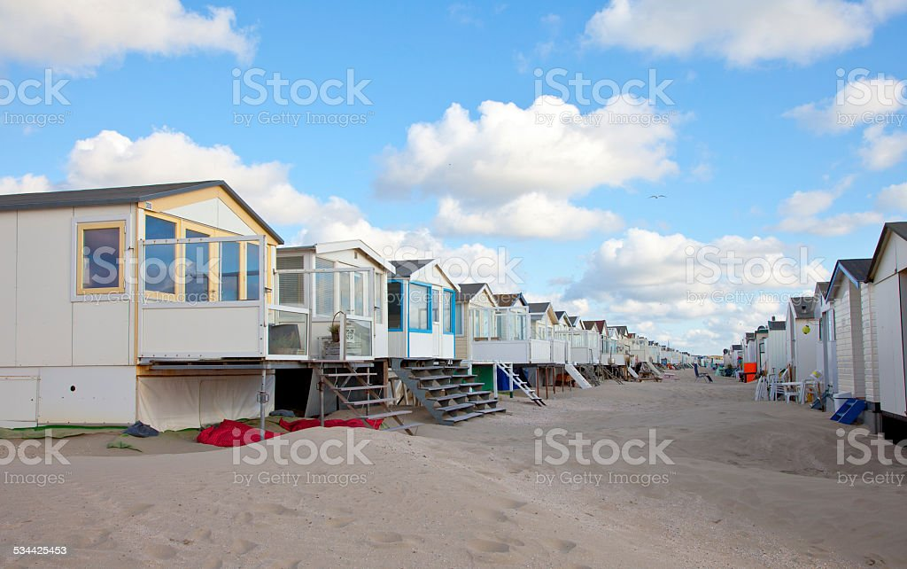Beach houses on beach in a row with blue sky stock photo