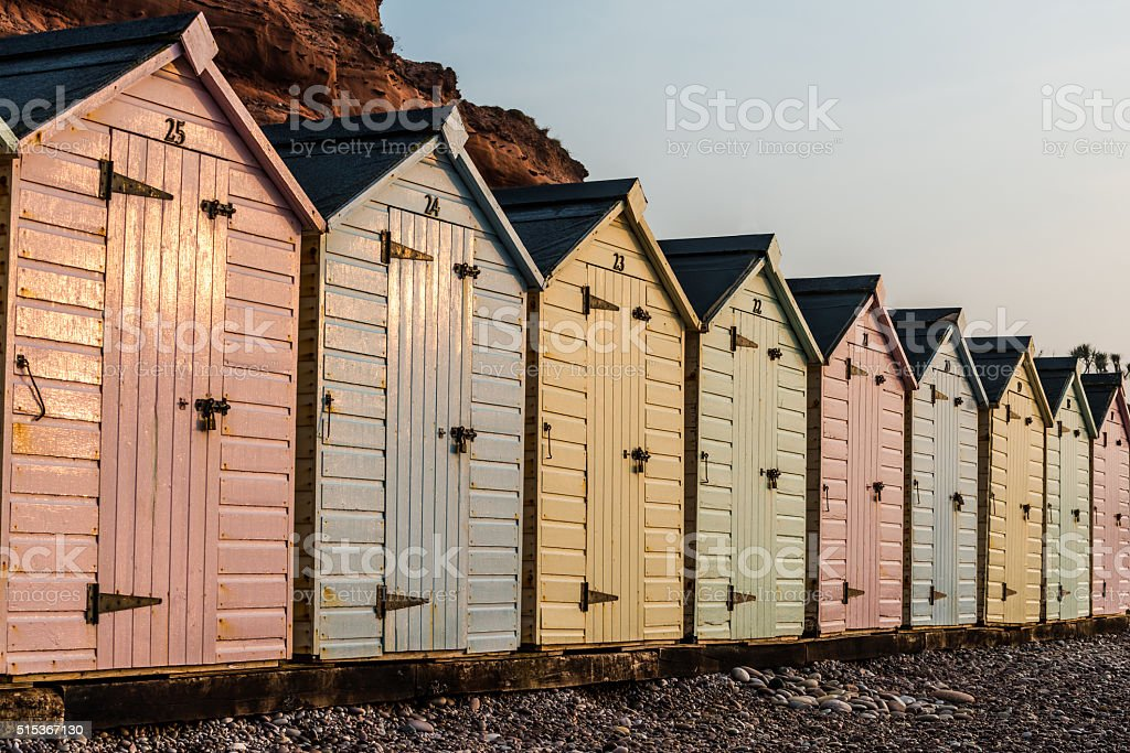 Beach hut row in pastel colors, red rock background stock photo